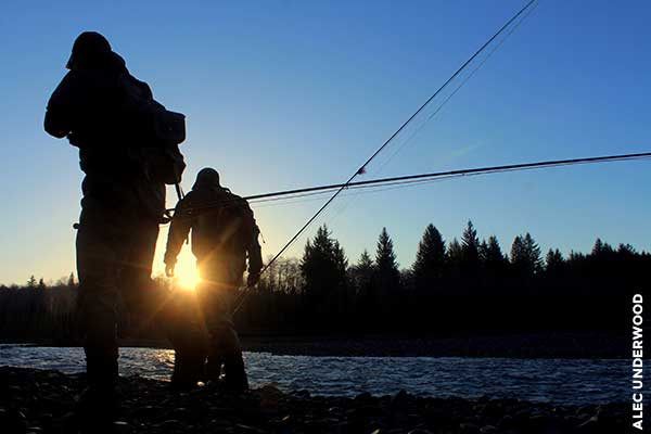 Two anglers walking at sunset.