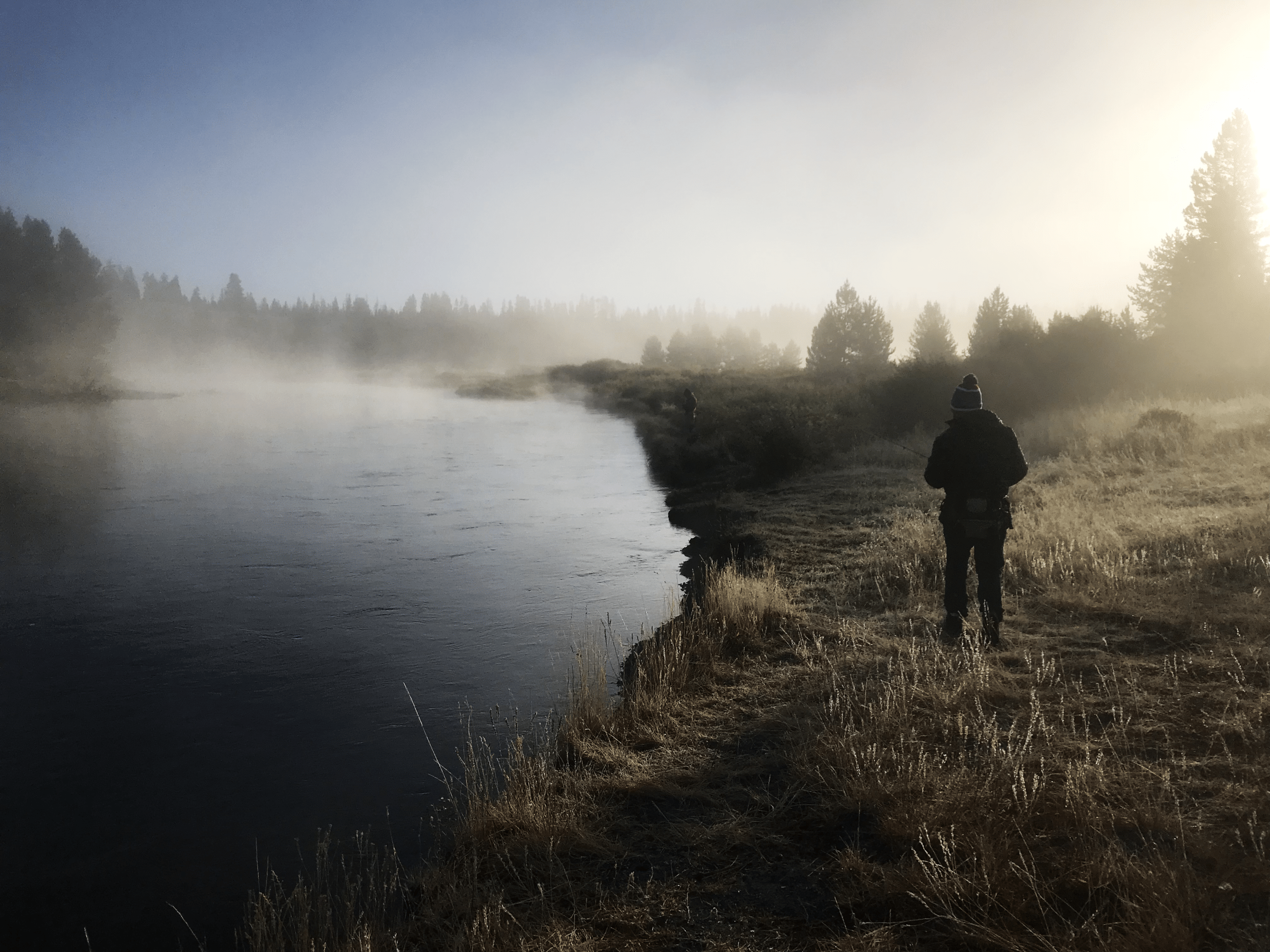 A angler stands on the bank of the Madison River