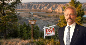 Pendley stands in front of the a for sale sign that is planted on public lands. lands in